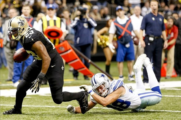 Nov 10, 2013; New Orleans, LA, USA; New Orleans Saints running back Pierre Thomas (23) escapes from Dallas Cowboys strong safety Jeff Heath (38) on a touchdown catch and run during the second quarter of a game at Mercedes-Benz Superdome. Mandatory Credit: Derick E. Hingle-USA TODAY Sports