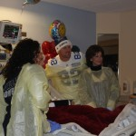 Jason Witten (center) and Gene Jones (right) visit a patient inside one of the rooms at Children's Medical in Dallas — Jordan Ross