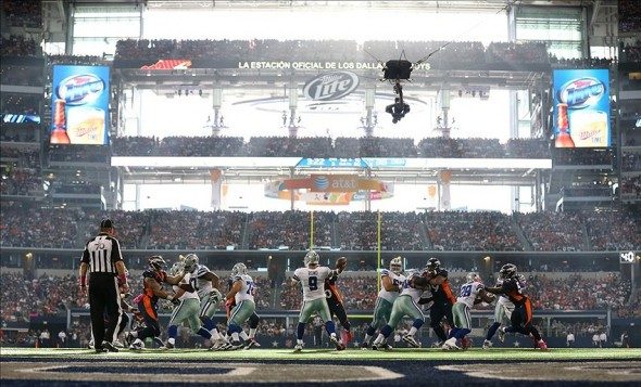 Oct 6, 2013; Arlington, TX, USA; Dallas Cowboys quarterback Tony Romo (9) throws in the pocket as sun rays enter the stadium in the third quarter against the Denver Broncos at AT