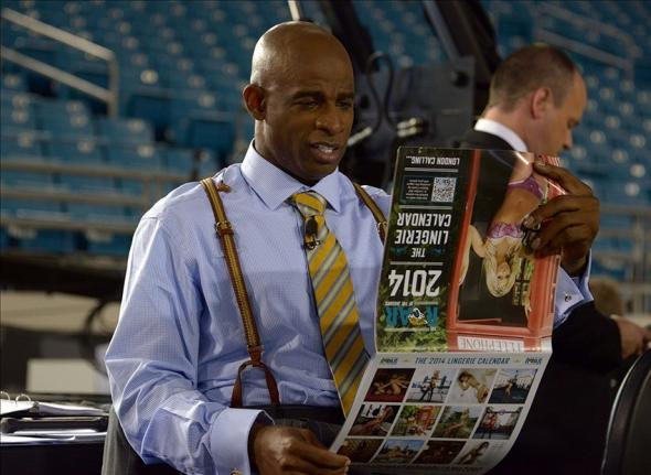 Dec 5, 2013; Jacksonville, FL, USA; Deion Sanders looks at the 2014 Jacksonville Jaguars roar cheerleaders lingerie calendar before the game against the Houston Texans at EverBank Field. Mandatory Credit: Kirby Lee-USA TODAY Sports