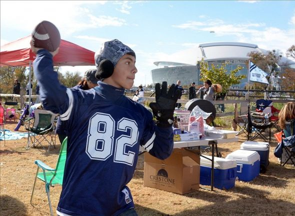 Nov 28, 2013; Arlington, TX, USA; Dallas Cowboys fan Kevin Guerra throws a football during tailgate festivities before a NFL football game on Thanksgiving against the Oakland Raiders at AT&T Stadium. Mandatory Credit: Kirby Lee-USA TODAY Sports
