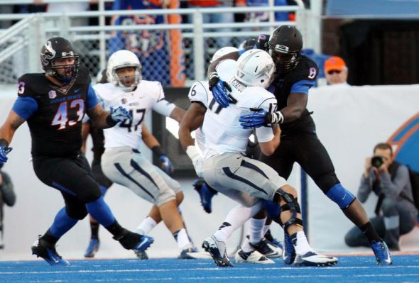 Oct 19, 2013; Boise, ID, USA; Nevada Pack quarterback Cody Fajardo (17) is tackled for loss by Boise State Broncos defensive end Demarcus Lawrence (8) during the first half against the Boise State Broncos at Bronco Stadium. Mandatory Credit: Brian Losness-USA TODAY Sports