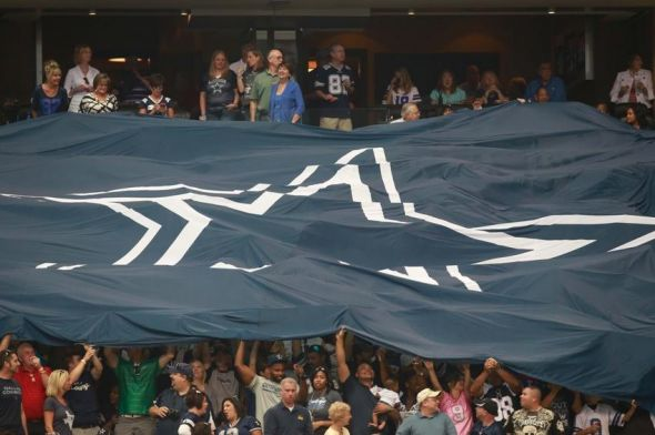 Sep 22, 2013; Arlington, TX, USA; Dallas Cowboys fans lift a flag with the star on it in the stands before the game against the St. Louis Rams at AT&T Stadium. The Dallas Cowboys beat the St. Louis Rams 31-7.Mandatory Credit: Tim Heitman-USA TODAY Sports