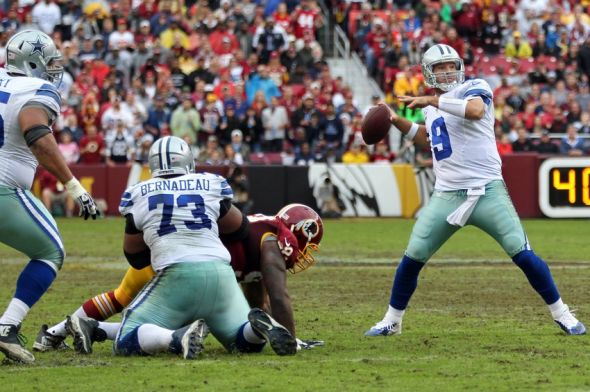 Dec 22, 2013; Landover, MD, USA; Dallas Cowboys quarterback Tony Romo (9) throws a touchdown pass as Washington Redskins defensive end Chris Baker (92) defends in the second quarter at FedEx Field. Mandatory Credit: Geoff Burke-USA TODAY Sports