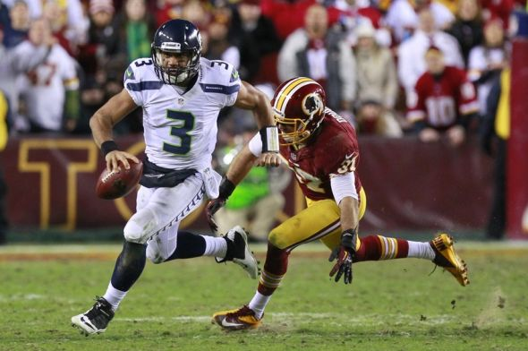 Jan 6, 2013; Landover, MD, USA; Seattle Seahawks quarterback Russell Wilson (3) runs with the ball as Washington Redskins strong safety Reed Doughty (37) chases in the fourth quarter of the NFC Wild Card playoff game at FedEx Field. The Seahawks win 24-14. Mandatory Credit: Geoff Burke-USA TODAY Sports