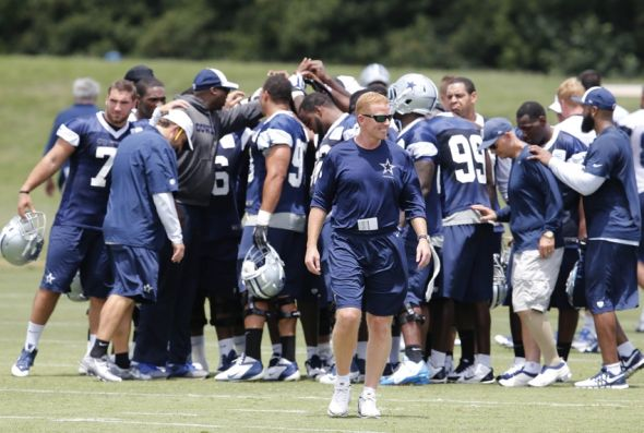 Jun 17, 2014; Dallas, TX, USA; Dallas Cowboys head coach Jason Garrett smiles as the team huddles during minicamp at Cowboys headquarters at Valley Ranch. Mandatory Credit: Matthew Emmons-USA TODAY Sports