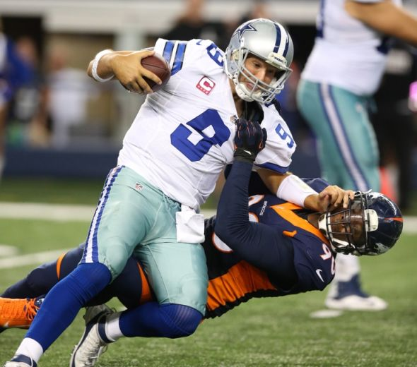 Oct 6, 2013; Arlington, TX, USA; Dallas Cowboys quarterback Tony Romo (9) is sacked in the fourth quarter by Denver Broncos defensive end Shaun Phillips (90) at AT&T Stadium. The Denver Broncos beat the Dallas Cowboys 51-48. Mandatory Credit: Matthew Emmons-USA TODAY Sports