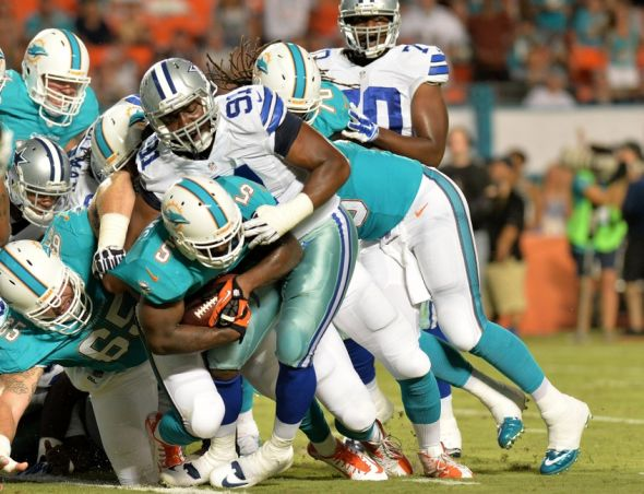 Aug 23, 2014; Miami Gardens, FL, USA; Miami Dolphins running back Damien Williams (5) scores a touchdown as Dallas Cowboys defensive end Kenneth Boatright (91) during the second half at Sun Life Stadium. Mandatory Credit: Steve Mitchell-USA TODAY Sports