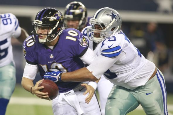 Aug 16, 2014; Arlington, TX, USA; Baltimore Ravens quarterback Keith Wenning (10) is tackled by Dallas Cowboys defensive tackle Zach Minter ((79) during the game at AT&T Stadium. Baltimore beat Dallas 37-30. Mandatory Credit: Tim Heitman-USA TODAY Sports