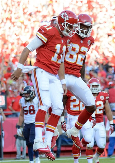 Oct 20, 2013; Kansas City, MO, USA; Kansas City Chiefs quarterback Alex Smith (11) and wide receiver Dwayne Bowe (82) celebrate after Smith