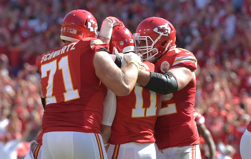Sep 11, 2016; Kansas City, MO, USA; Kansas City Chiefs quarterback Alex Smith (11) is congratulated by offensive lineman Mitchell Schwartz (71) and wide receiver Albert Wilson (12) after scoring the winning touchdown in overtime against the San Diego Chargers at Arrowhead Stadium. The Chiefs won 33-27 in overtime. Mandatory Credit: Denny Medley-USA TODAY Sports
