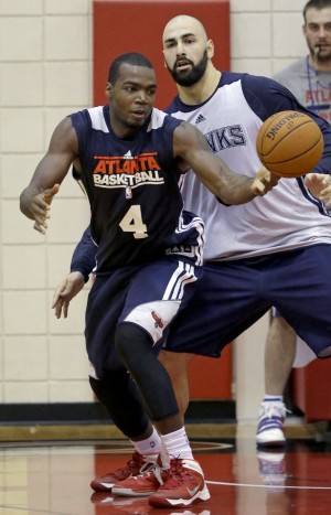 Atlanta Hawks' Paul Millsap, left, handles the ball against teammate Pero Antic, of Macedonia, during NBA basketball training camp, Tuesday, Oct. 1, 2013, in Athens, Ga. (AP Photo/David Goldman)