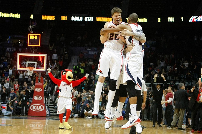 Dec 13, 2013; Atlanta, GA, USA; Atlanta Hawks shooting guard Kyle Korver (26) and center Al Horford (15) celebrate a victory against the Washington Wizards in overtime at Philips Arena. The Hawks defeated the Wizards 101-99. Mandatory Credit: Brett Davis-USA TODAY Sports