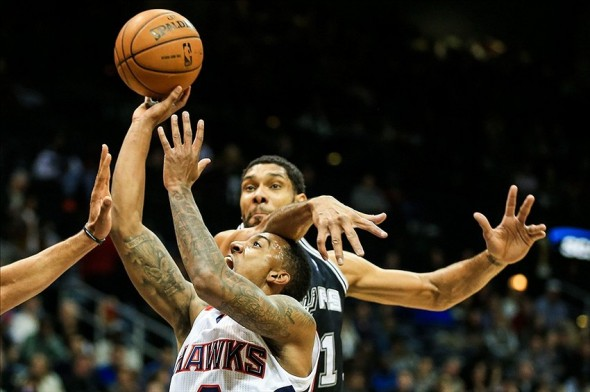 Jan 24, 2014; Atlanta, GA, USA; Atlanta Hawks point guard Jeff Teague (0) shoots a basket past San Antonio Spurs power forward Tim Duncan (21) in the first quarter against the San Antonio Spurs at Philips Arena. Mandatory Credit: Daniel Shirey-USA TODAY Sports