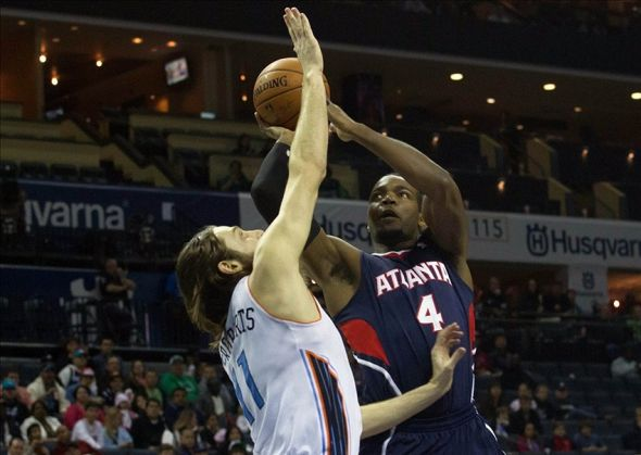 Mar 17, 2014; Charlotte, NC, USA; Atlanta Hawks forward Paul Millsap (4) goes up for a shot over Charlotte Bobcats forward Josh McRoberts (11) during the first half at Time Warner Cable Arena. Mandatory Credit: Jeremy Brevard-USA TODAY Sports