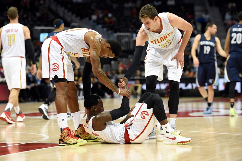 Oct 21, 2015; Atlanta, GA, USA; Atlanta Hawks guard Dennis Schroder (17) is helped up after a fall by guard Kent Bazemore (24) and forward Mike Muscala (31) during the game against the Memphis Grizzlies during the first half at Philips Arena. Mandatory Credit: Dale Zanine-USA TODAY Sports