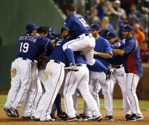 Aug 12, 2014; Arlington, TX, USA; Texas Rangers shortstop Adam Rosales (center) is swarmed by teammates after his bases loaded walk to win over the Tampa Bay Rays following the 14th inning of a baseball game at Globe Life Park in Arlington. Rangers won 3-2. Mandatory Credit: Jim Cowsert-USA TODAY Sports
