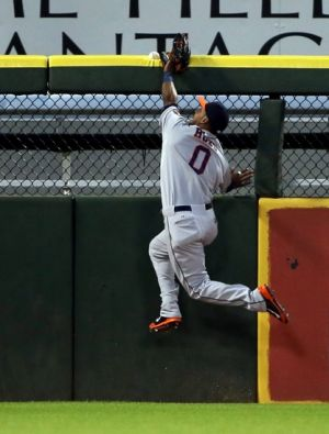 Jul 18, 2014; Chicago, IL, USA; Houston Astros left fielder L.J. Hoes (0) leaps and watches as a ball hit by Chicago White Sox designated hitter Adam Dunn (not pictured) bounces off the top of the wall and back into play for a double during the fourth inning at U.S Cellular Field. Mandatory Credit: Jerry Lai-USA TODAY Sports