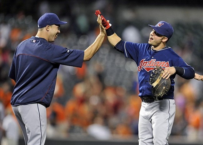 Jun 24, 2013; Baltimore, MD, USA; Cleveland Indians starting pitcher Ubaldo Jimenez (left) is congratulated by first baseman Nick Swisher (right) after a game against the Baltimore Orioles at Oriole Park at Camden Yards. The Indians defeated the Orioles 5-2. Mandatory Credit: Joy R. Absalon-USA TODAY Sports