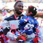 Feb 7, 2012; East Rutherford, NJ, USA; New York Giants defensive end Justin Tuck holds his son Jayce Tuck as confetti falls during the Super Bowl XLVI victory celebration at MetLife Stadium. Mandatory Credit: Ed Mulholland-US PRESSWIRE
