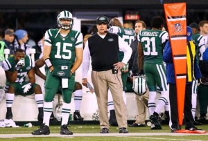 Jets' QB Tim Tebow (#15) observes the game while standing next to Jets HC Rex Ryan on the sidelines.