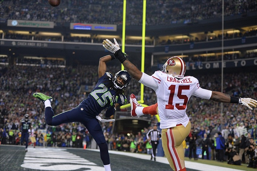 Jan 19, 2014; Seattle, WA, USA; Seattle Seahawks cornerback Richard Sherman (25) tips the ball against San Francisco 49ers wide receiver Michael Crabtree (15) for an interception by Seahawks outside linebacker Malcolm Smith (not pictured) during the fourth quarter of the 2013 NFC Championship football game at CenturyLink Field. Mandatory Credit: Kyle Terada-USA TODAY Sports