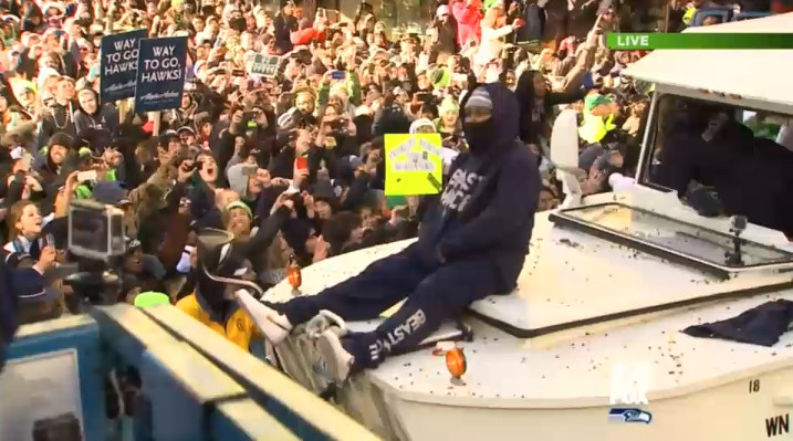 Marshawn Lynch riding on the duck chucking out skittles to the crowd
