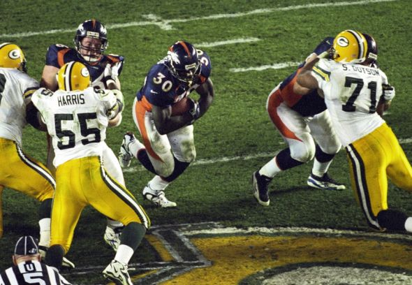 Jan 25, 1998; San Diego, CA, USA; FILE PHOTO; Denver Broncos running back Terrell Davis (30) carries the ball past Green Bay Packers linebacker Bernardo Harris (55) and defensive tackle Santana Dotson (71) during Super Bowl XXXII at Qualcomm Stadium. The Broncos defeated the Packers 31-24. Mandatory Credit: Peter Brouillet-USA TODAY Sports