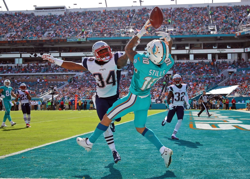 Jan 3, 2016; Miami Gardens, FL, USA; Miami Dolphins wide receiver Kenny Stills (10) is unable to make a catch in the end zone as New England Patriots cornerback Leonard Johnson (34) defends the play during the first half at Sun Life Stadium. Mandatory Credit: Steve Mitchell-USA TODAY Sports
