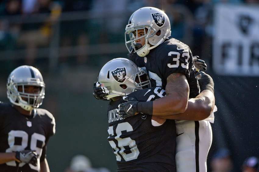 Oakland Raiders running back DeAndre Washington (33) celebrates with Raiders guard Gabe Jackson (66) after scoring a touchdown against the Tennessee Titans during the first half at Oakland-Alameda Coliseum.