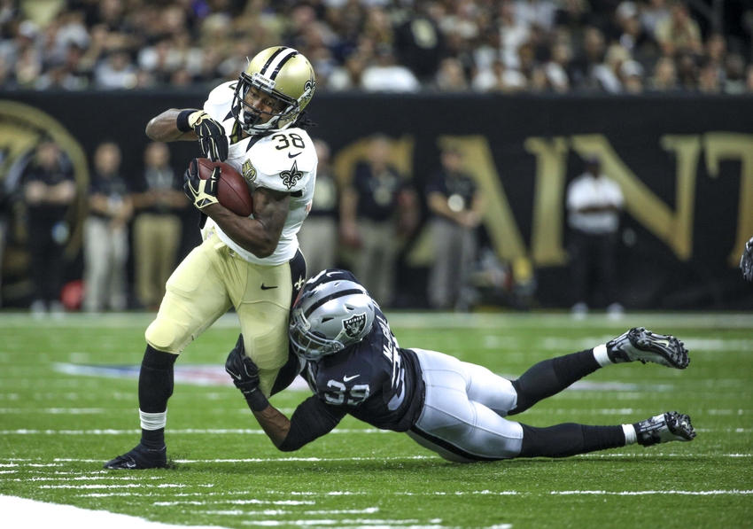 New Orleans Saints running back Travaris Cadet (38) is tackled by Oakland Raiders cornerback Keith McGill (39) during the second quarter of a game at the Mercedes-Benz Superdome.