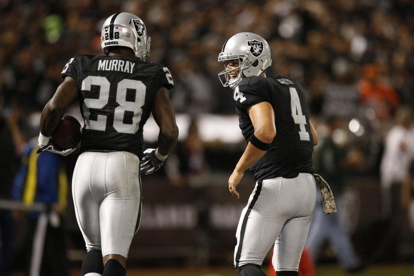 Oakland Raiders quarterback Derek Carr (4) congratulates running back Latavius Murray (28) after Murray rushed for a touchdown against the Denver Broncos in the second quarter at Oakland Coliseum.