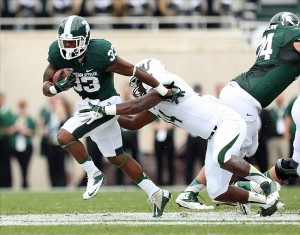 Sep 7, 2013; East Lansing, MI, USA; Michigan State Spartans running back Jeremy Langford (33) runs the ball against South Florida Bulls linebacker Devekeyan Lattimore (34) during the first quarter at Spartan Stadium. Mandatory Credit: Mike Carter-USA TODAY Sports