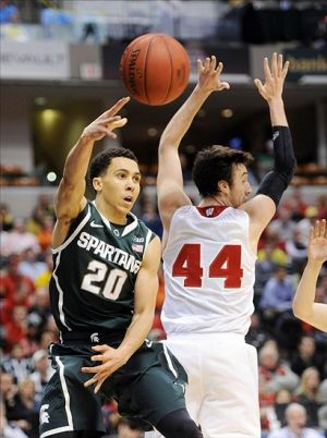 Mar 15, 2014; Indianapolis, IN, USA; Michigan State Spartans guard Travis Trice (20) makes a pass against Wisconsin Badgers forward Frank Kaminski (44) in the semifinals of the Big Ten college basketball tournament at Bankers Life Fieldhouse.