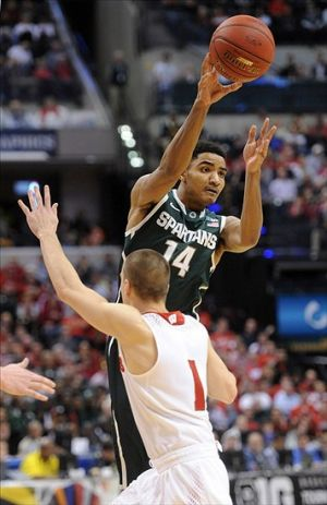 Mar 15, 2014; Indianapolis, IN, USA; Michigan State Spartans guard Gary Harris (14) makes a pass against Wisconsin Badgers guard Ben Brust (1) in the semifinals of the Big Ten college basketball tournament at Bankers Life Fieldhouse.