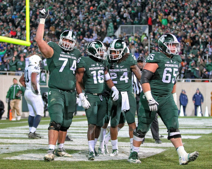 Nov 28, 2015; East Lansing, MI, USA; Michigan State Spartans offensive tackle Jack Conklin (74) and Michigan State Spartans wide receiver Aaron Burbridge (16) and Michigan State Spartans running back Gerald Holmes (24) and Michigan State Spartans offensive lineman Brian Allen (65) celebrate a touchdown during the 2nd half of a game against the Penn State Nittany Lions at Spartan Stadium. Mandatory Credit: Mike Carter-USA TODAY Sports