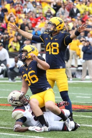 Sep 13, 2014; College Park, MD, USA; West Virginia Mountaineers kicker Josh Lambert (86) and holder Michael Molinari (48) watch the game winning field goal over the Maryland Terrapins at Byrd Stadium. Mandatory Credit: Mitch Stringer-USA TODAY Sports