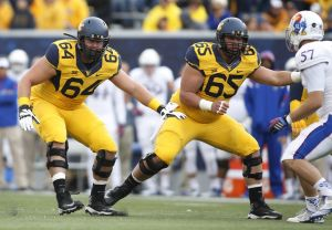Oct 4, 2014; Morgantown, WV, USA; West Virginia Mountaineers offensive linemen Mark Glowinski (64) and Tyler Orlosky (65) block at the line of scrimmage against the Kansas Jayhawks at Milan Puskar Stadium. West Virginia won 33-14. Mandatory Credit: Charles LeClaire-USA TODAY Sports