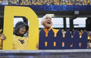 Oct 4, 2014; Morgantown, WV, USA; West Virginia Mountaineers fans Jeremy Hyde (left) and his grandmother Jody Payne (right) cheer on the Mountaineer defense against the Kansas Jayhawks during the third quarter at Milan Puskar Stadium. The Mountaineers won 33-14. Mandatory Credit: Charles LeClaire-USA TODAY Sports