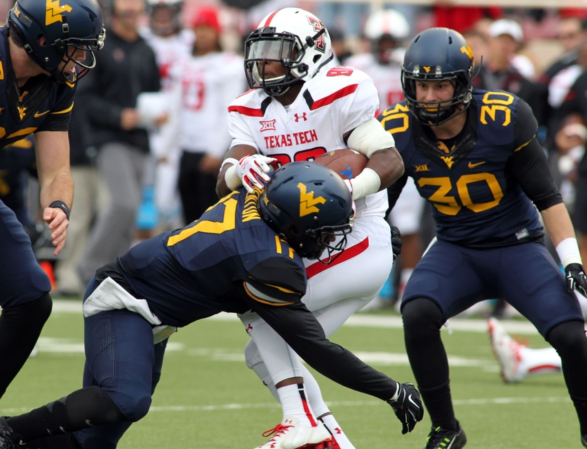 Oct 11, 2014; Lubbock, TX, USA; Texas Tech Red Raiders wide receiver Cameron Batson (80) is tackled by West Virginia Mountaineers defensive back Al-Rasheed Benton (17) in the first half at Jones AT&T Stadium. Mandatory Credit: Michael C. Johnson-USA TODAY Sports