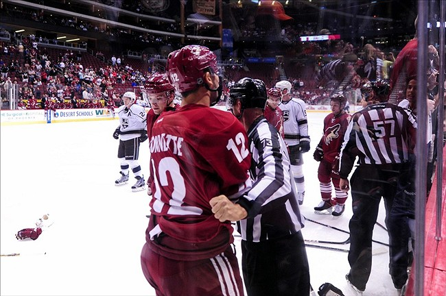 Sep 15, 2013; Glendale, AZ, USA; NHL linesman Vaughan Rody (73) restrains Phoenix Coyotes defenseman Paul Bissonnette (12) during the first period against the Los Angeles Kings at Jobing.com Arena. Mandatory Credit: Matt Kartozian-USA TODAY Sports