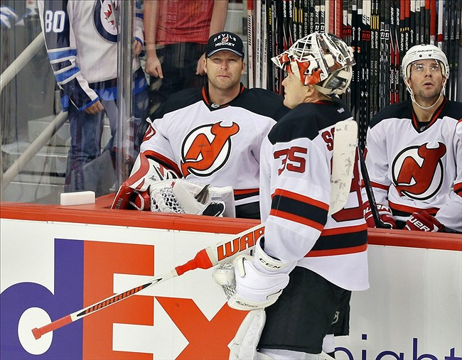 Oct 13, 2013; Winnipeg, Manitoba, CAN; New Jersey Devils goalie Cory Schneider (35) speaks with goalie Martin Brodeur (30) during a break in the third period against the Winnipeg Jets at MTS Centre. Jets win 3-0. Mandatory Credit: Bruce Fedyck-USA TODAY Sports
