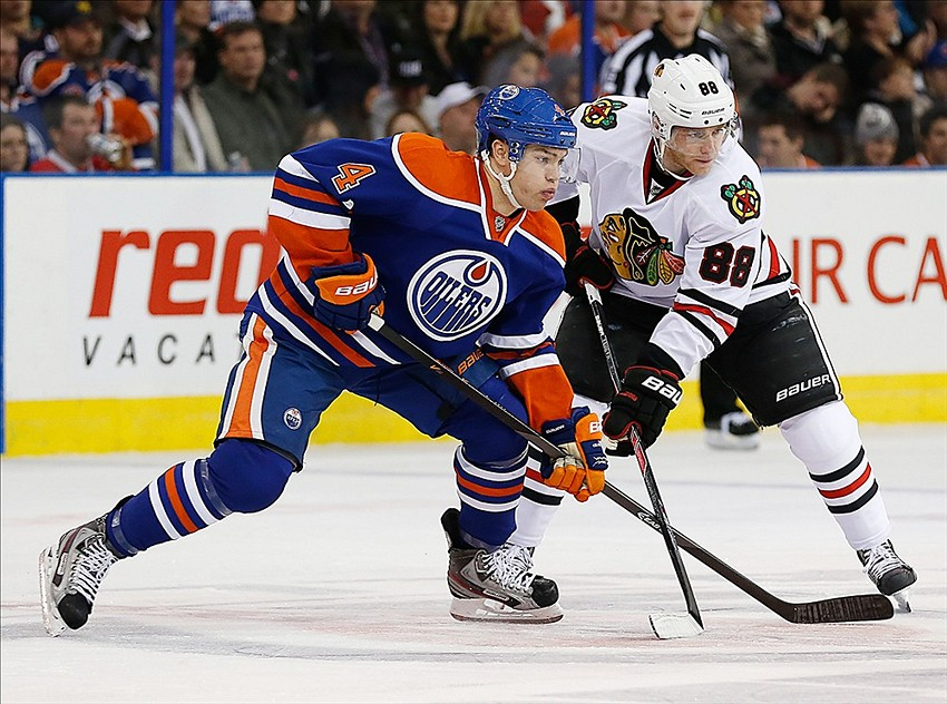 Nov 25, 2013; Edmonton, Alberta, CAN; Edmonton Oilers forward Taylor Hall (4) and Chicago Blackhawks forward Patrick Kane (88) battle for a loose puck during the second period at Rexall Place. Mandatory Credit: Perry Nelson-USA TODAY Sports