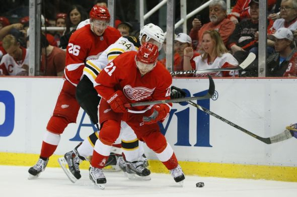 Apr 22, 2014; Detroit, MI, USA; Detroit Red Wings left wing Tomas Tatar (21) battles for the puck with Boston Bruins center Carl Soderberg (34) in the third period in game three of the first round of the 2014 Stanley Cup Playoffs at Joe Louis Arena. The Bruins won 3-0. Mandatory Credit: Rick Osentoski-USA TODAY Sports
