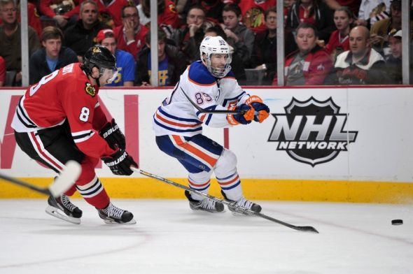 Nov 10, 2013; Chicago, IL, USA; Edmonton Oilers center Sam Gagner (89) shoots the puck against Chicago Blackhawks defenseman Nick Leddy (8) during the third period at the United Center. The Blackhawks beat the Oilers 5-4. Mandatory Credit: Rob Grabowski-USA TODAY Sports