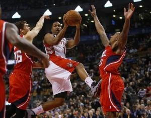 Feb 12, 2014; Toronto, Ontario, CAN; Toronto Raptors guard Kyle Lowry (7) goes to make a pass in between Atlanta Hawks guard-forward Kyle Korver (26) and guard Jeff Teague (0) during the first half at the Air Canada Centre. Mandatory Credit: John E. Sokolowski-USA TODAY Sports