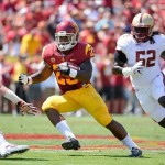 Sep 14, 2013; Los Angeles, CA, USA; USC Trojans running back Tre Madden (23) runs between Boston College Eagles defensive back Sean Sylvia (19), linebacker Steven Daniels (52) and defensive back Bryce Jones (17) to pick up 16 yards during first quarter action at Los Angeles Memorial Coliseum. Mandatory Credit: Robert Hanashiro-USA TODAY Sports