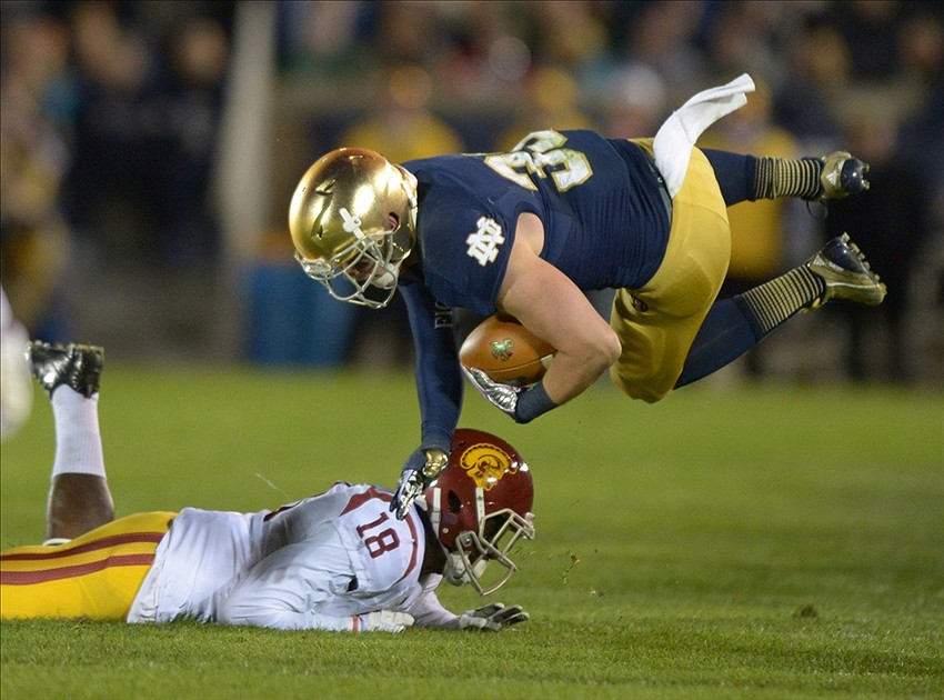 Oct 19, 2013; South Bend, IN, USA; Notre Dame Fighting Irish running back Cam McDaniel (33) is tackled by Southern California Trojans linebacker Dion Bailey (18) at Notre Dame Stadium. Notre Dame defeated USC 14-10. Mandatory Credit: Kirby Lee-USA TODAY Sports