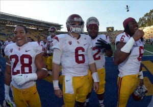 Nov 9, 2013; Berkeley, CA, USA; Southern California Trojans players Ryan Dillard (28), Cody Kessler (6), Khaliel Rodgers (62) and Josh Shaw (6) celebrate at the end of the game against the California Golden Bears at Memorial Stadium. USC defeated California 62-28. Mandatory Credit: Kirby Lee-USA TODAY Sports