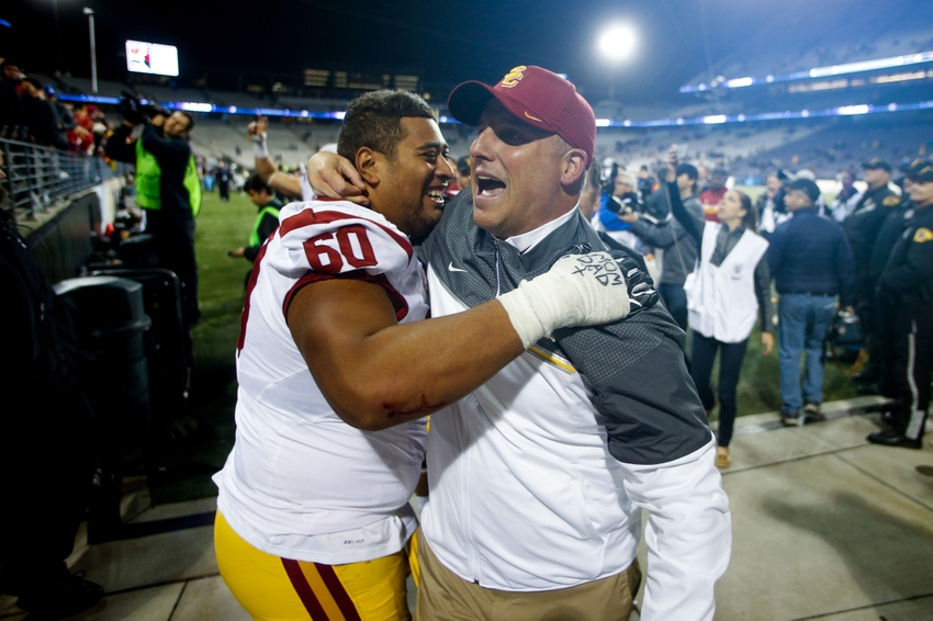 Nov 12, 2016; Seattle, WA, USA; USC Trojans head coach Clay Helton celebrates with guard Viane Talamaivao (60) following a 26-13 victory against the Washington Huskies at Husky Stadium. Mandatory Credit: Joe Nicholson-USA TODAY Sports